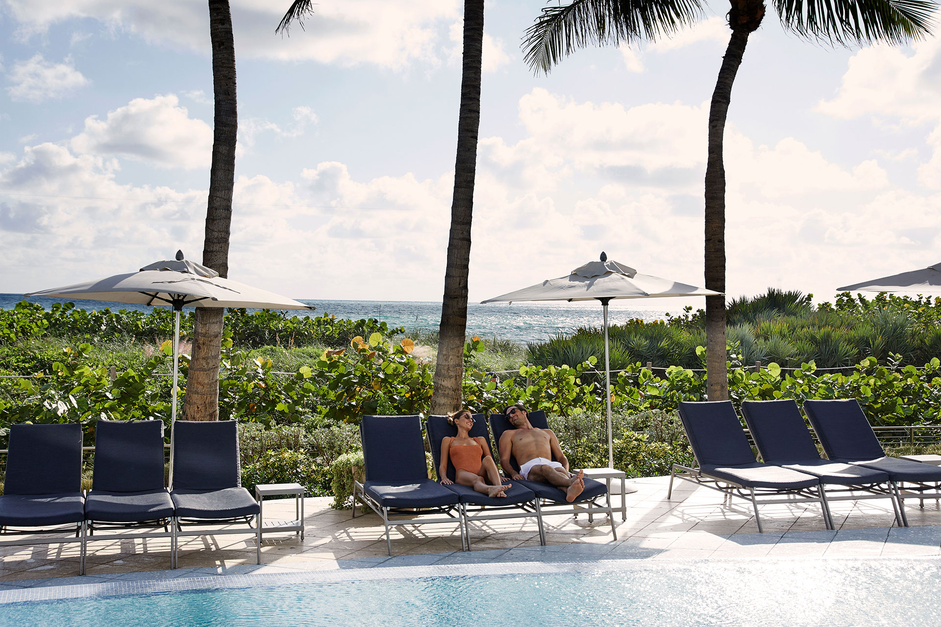 a man and a woman in swimwear lounge of blue pool chairs next to a pool. They are under a white umbrella. In the background is greenery and palm trees. The ocean peaks out in the distance.