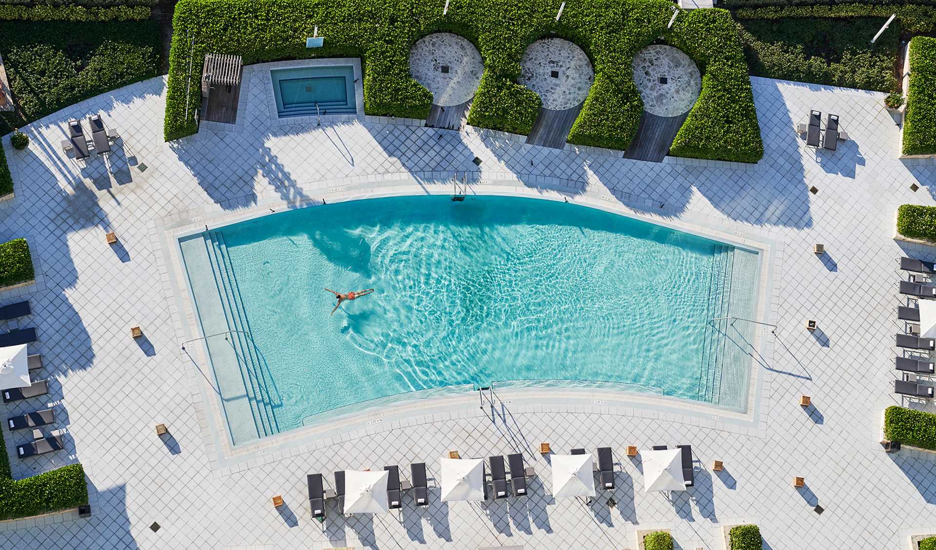 aerial image of a pool surrounded by white tile and lush green manicured bushes. Off to the side is a hot tub. There are gray lounge chairs adn white umbrellas lining the edge of the pool.