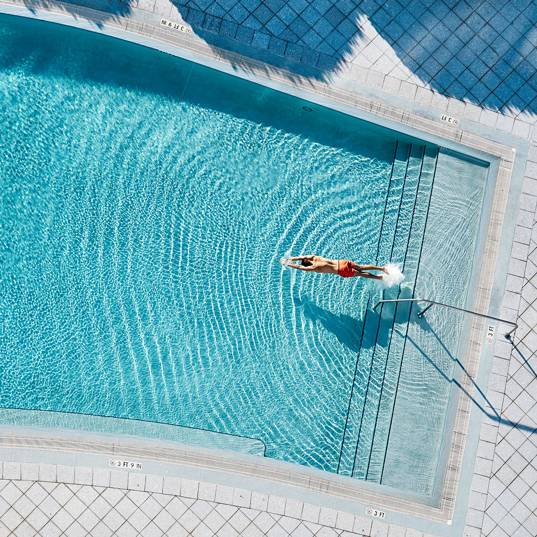Aerial shot of of a man in red bathing shorts diving into a pool to swim laps/