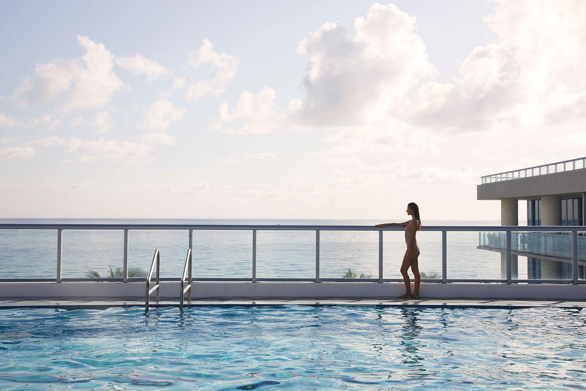 a woman in a bathing suit stands looking out over a balcony. There view is of the ocean and the resort grounds. In the foreground is a long swimming pool
