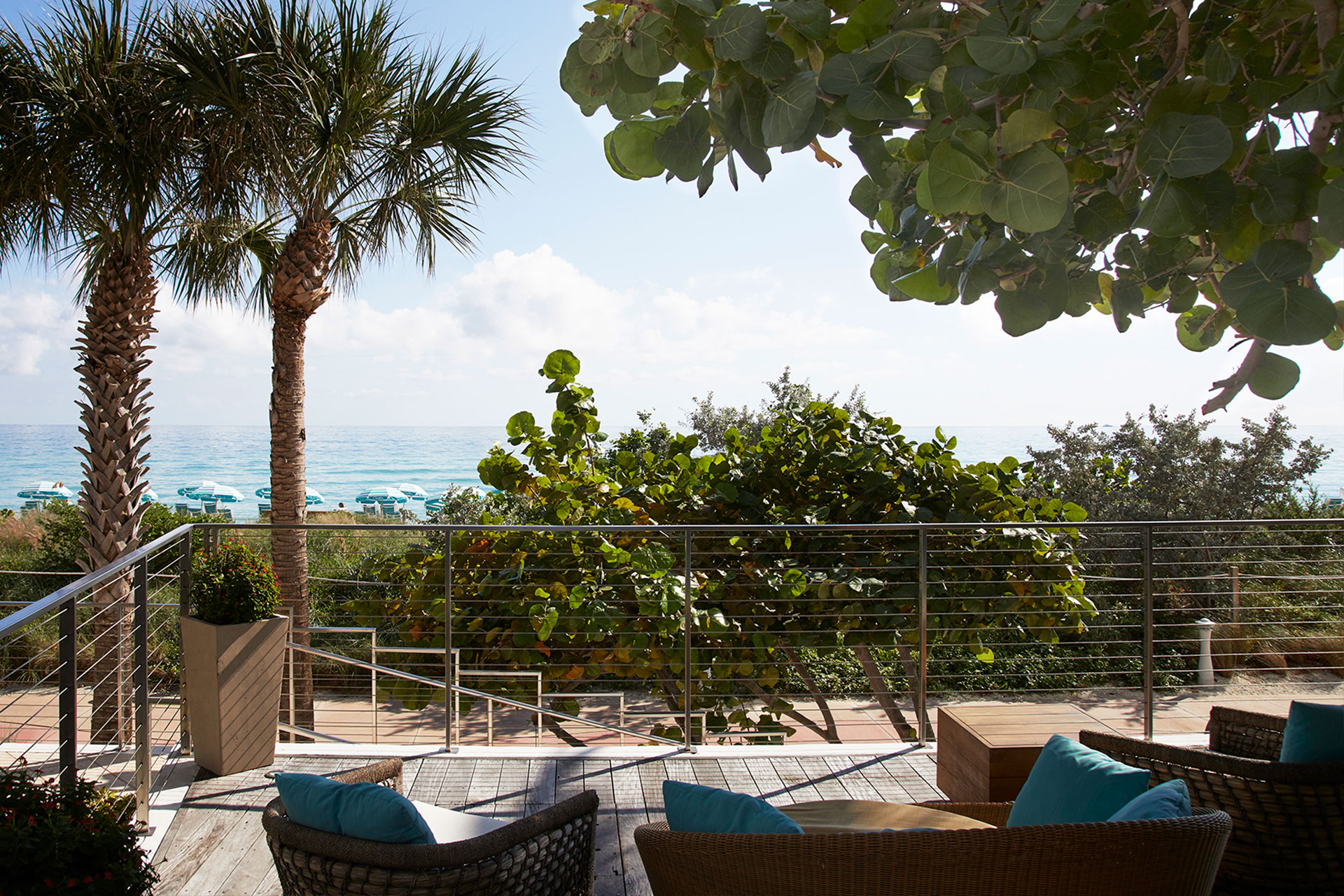 Image of an outdoor seating area. There are woven chairs and couches with blue throw pillows on a balcony. The balcony is surrounded by greenery such as palm tress and bushes. There is a view of the ocean and the beach chairs and umbrellas that line the sand.