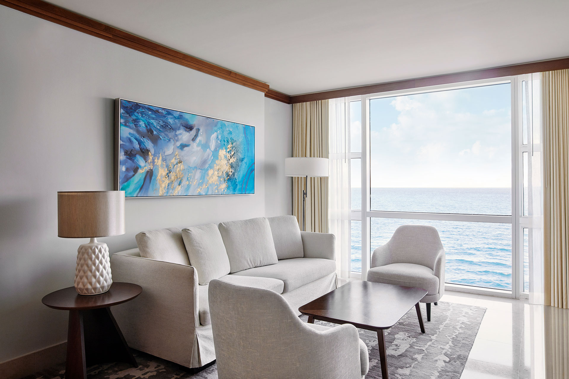 a sitting room in a suite with an ocean view. There is a light colored couch against the wall with a blue painting overhead. There are two chairs with the same fabric on either side of the couch circling a dark wood table.