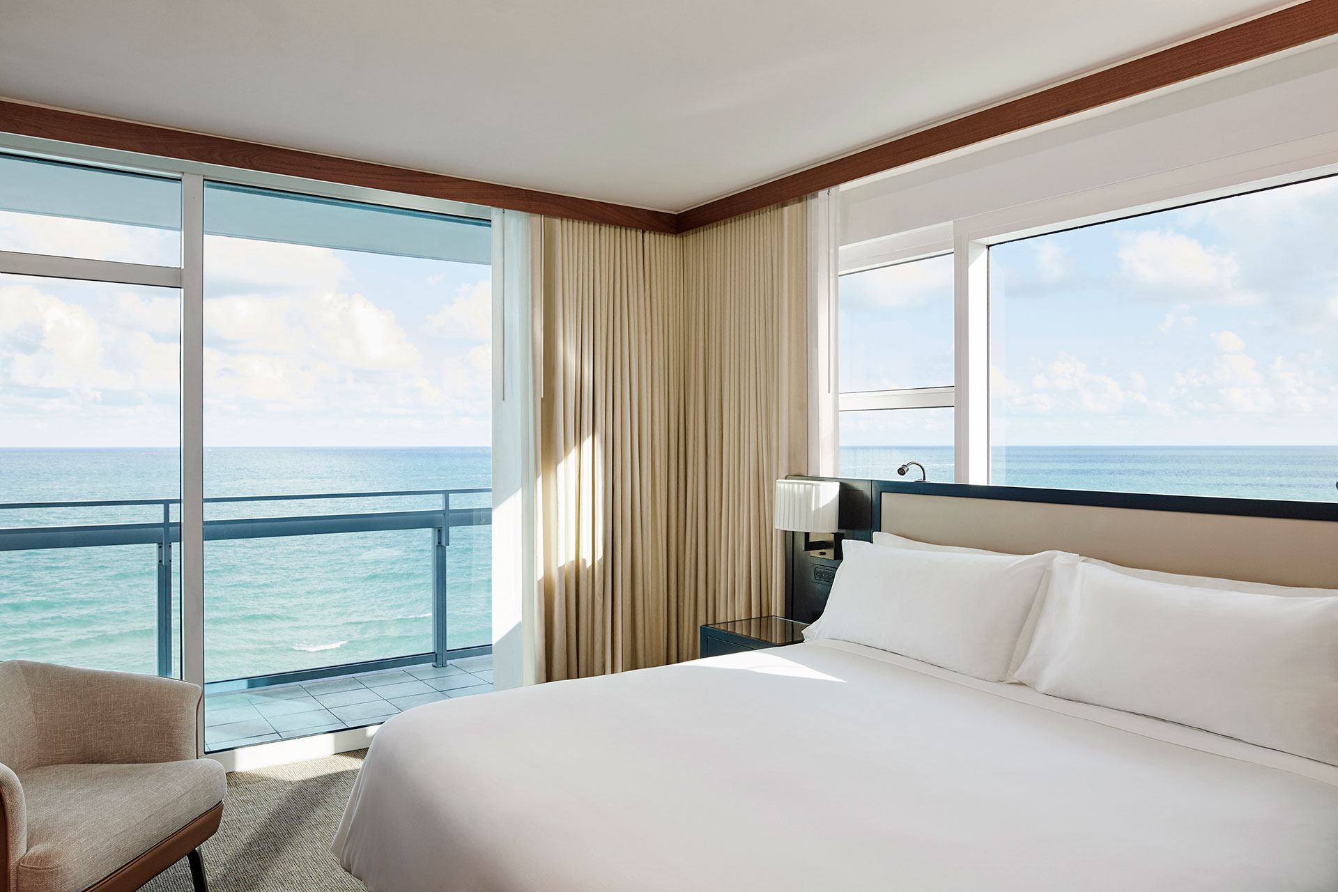 an ocean view suite with a balcony. The bed is on the right side of the room with crisp white linens. There is a black bedside table and a light colored chair in the left corner.
