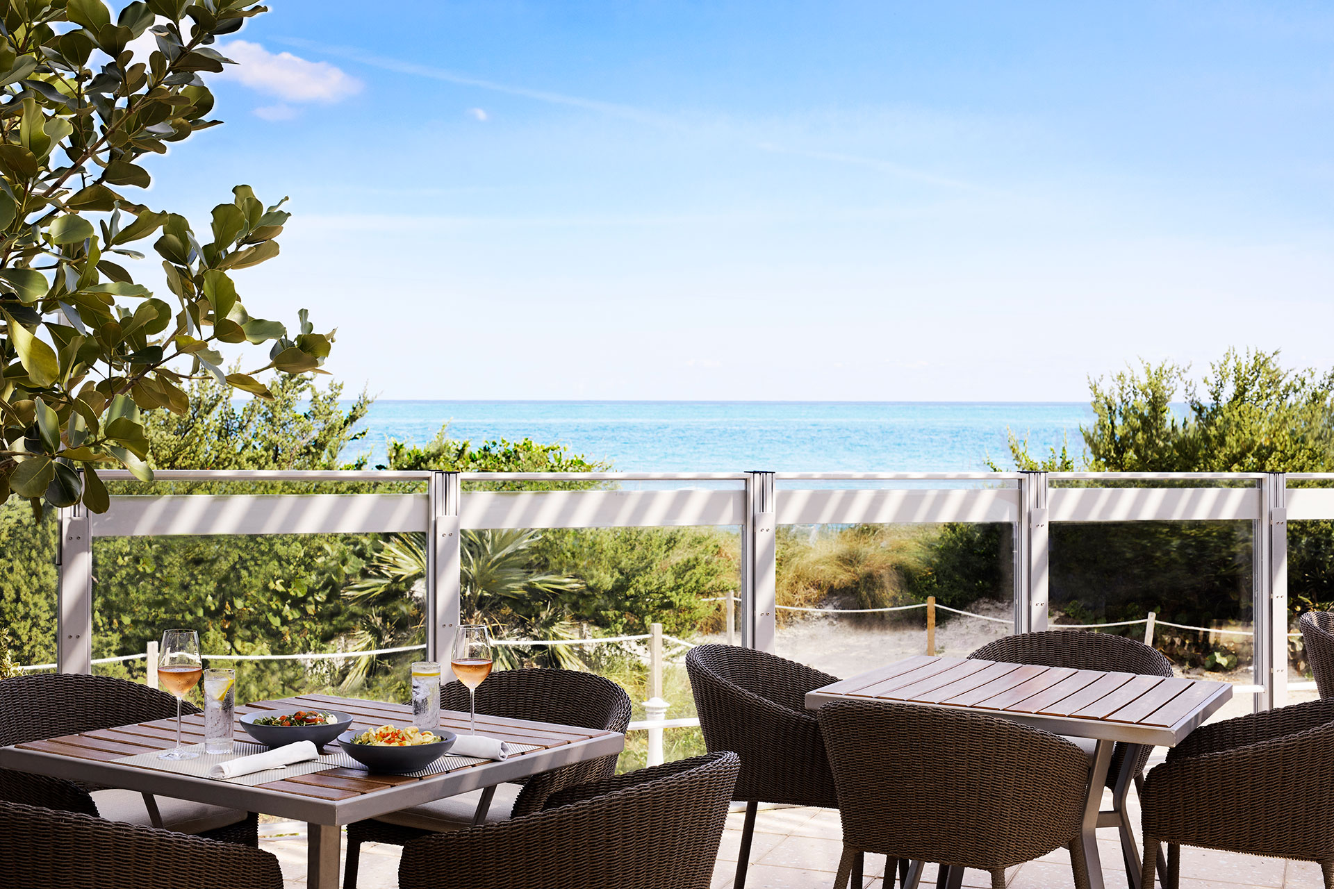 photo of an outdoor dining area. The chairs are woven brown and the tables are a dark wood. At on table there is a glass of rose at each place setting and there are two gray bowls of food in the middle of the table. The outdoor seating area overlooks the sand dunes and the ocean