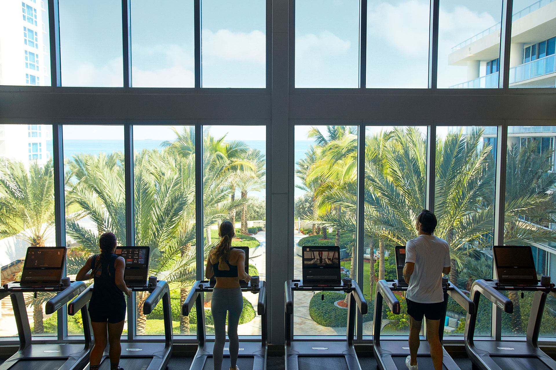 Image of the gym facilities. The shot focuses on the treadmills. There are six treadmills lined against full length windoes with a video of a courtyard that leads to the beach. There are three people in workout outfits running on the treadmills, two woman and one man.