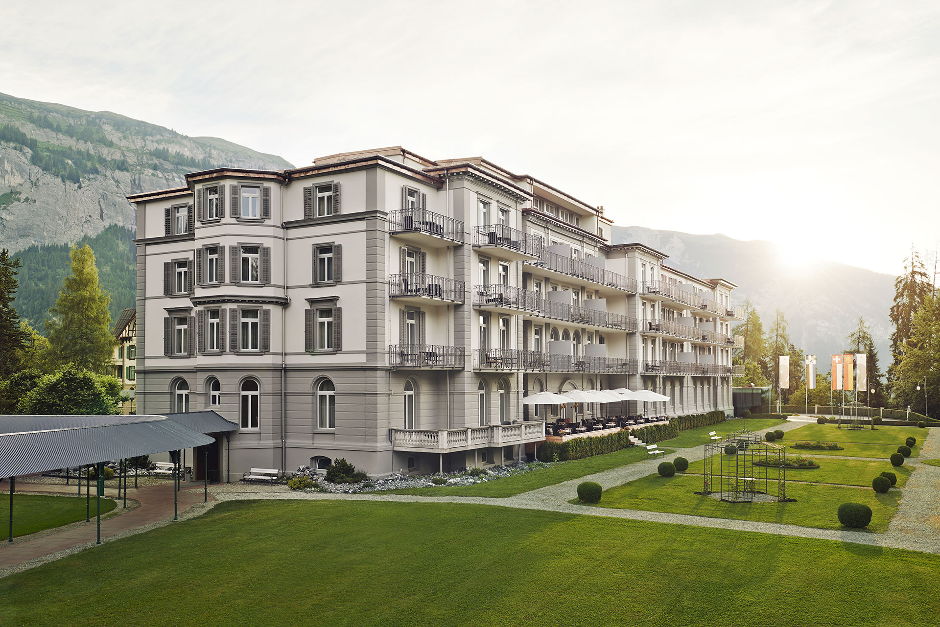 exterior shot of the Waldhaus Flims resort building and the surrounding grounds. The building is white with gray shutters. There are balconies at each window. The grounds are lush green grass with manicured bushes. In the background are the swiss alps.