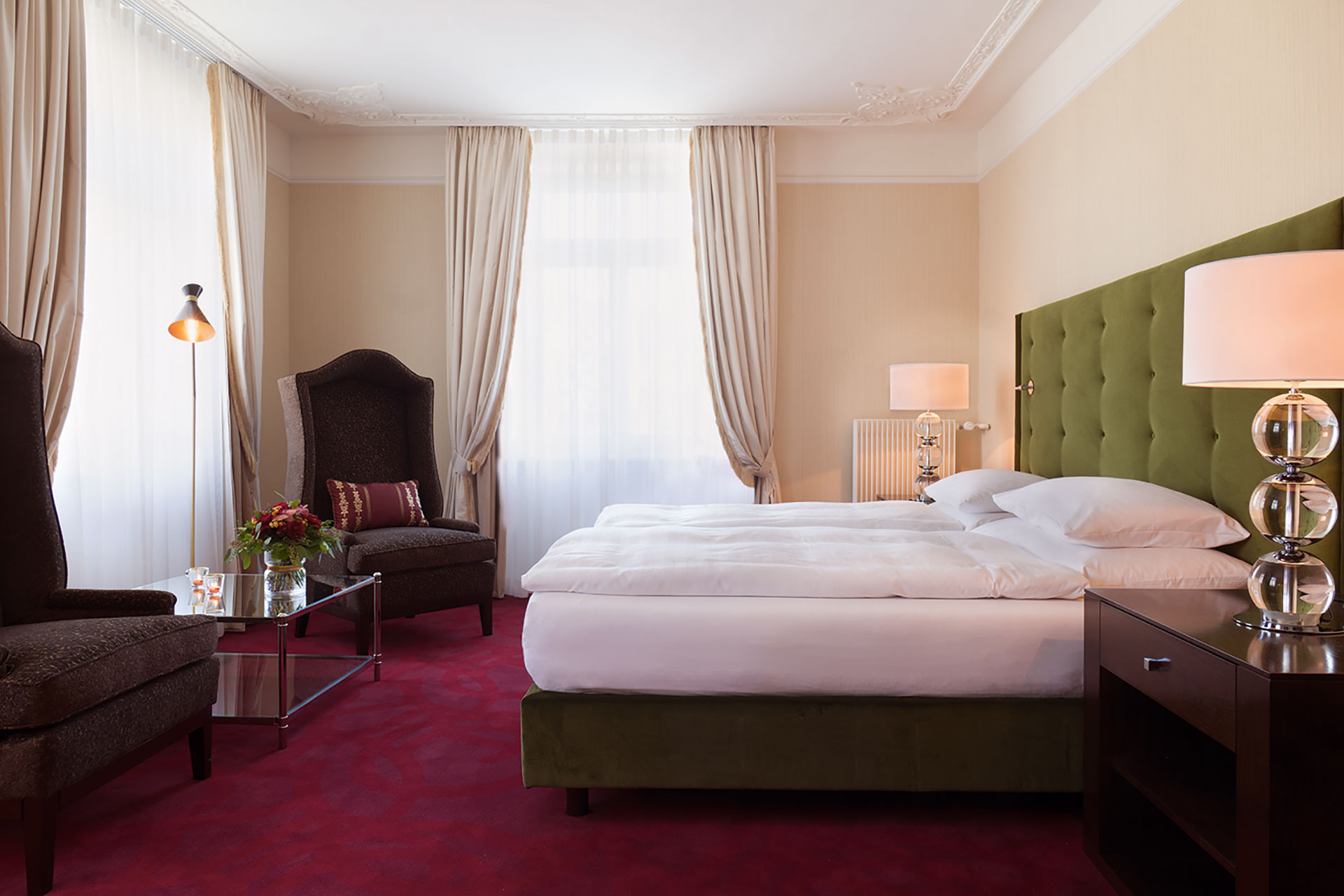 An interior shot of a one bed suite. The bed is donned in white linens and the headboard is a dark green. The carpet is red and the two high back chairs in each corner of the room are brown. There are two bedside tables with lamps on top of them.