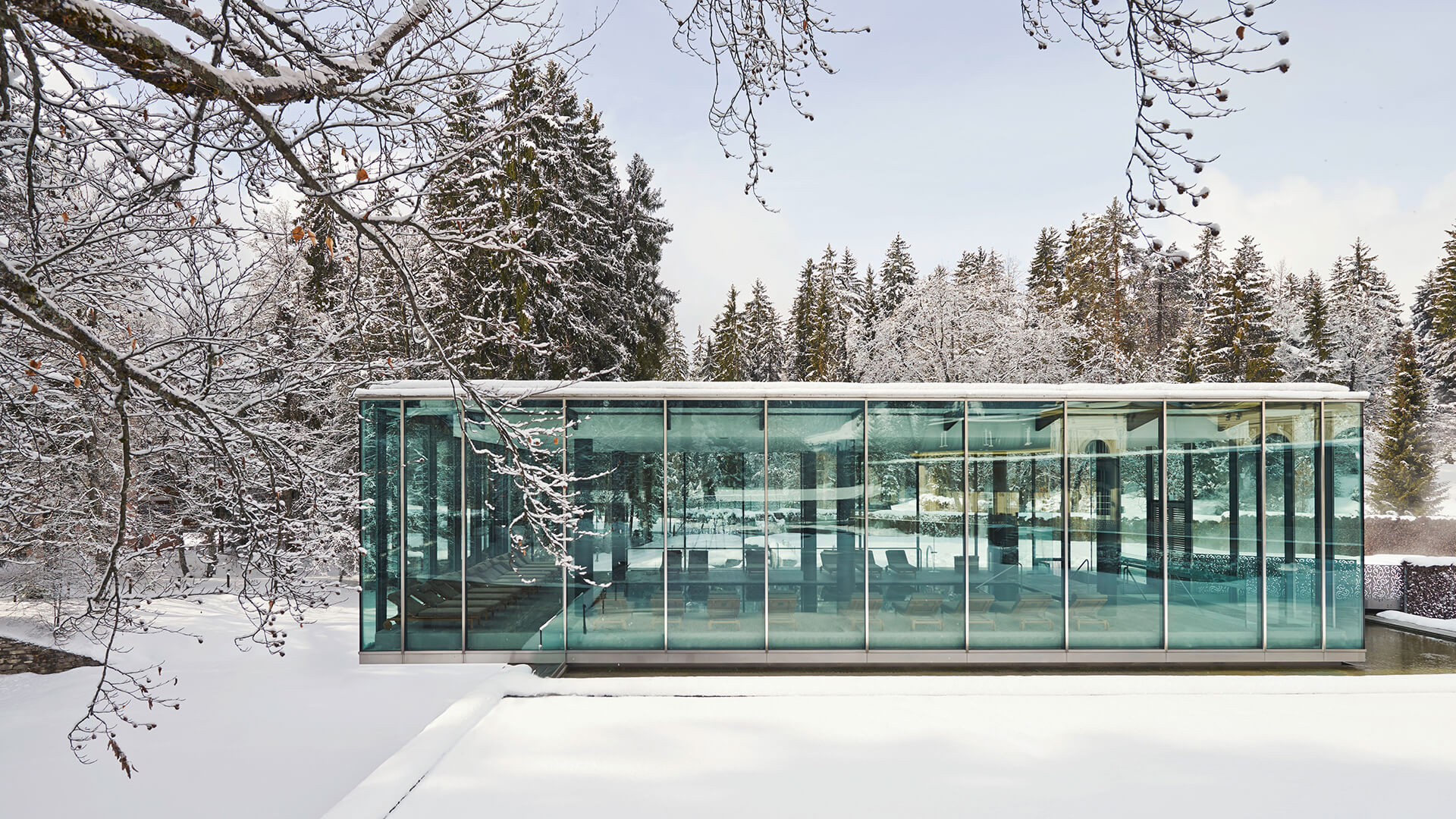 beautiful winter scene of the Waldhaus Spa glass building, white snow on the ground and surrounding trees, clear blue sky in the background