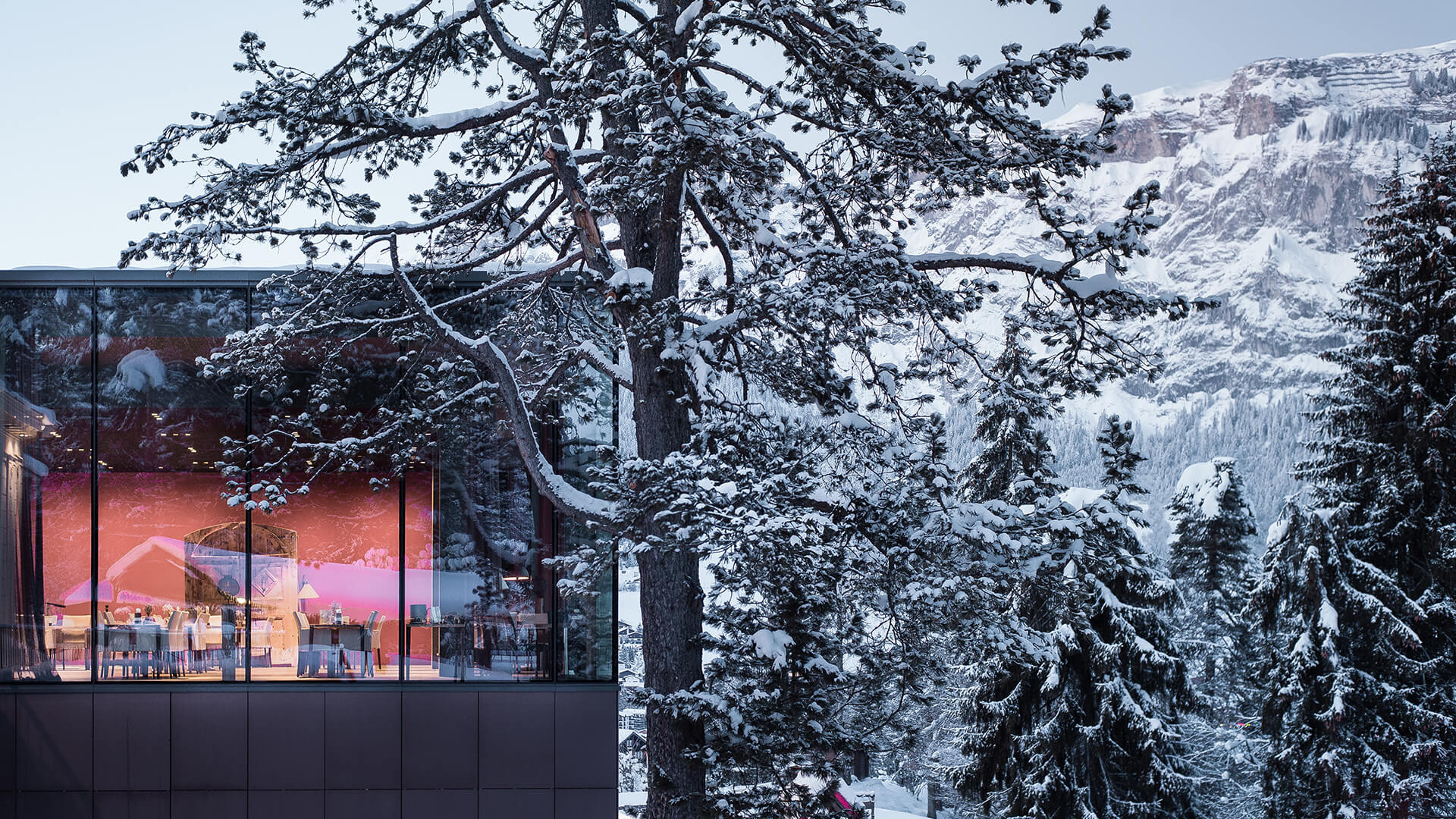 Beautiful Epoca restaurant exterior surrounded by snow cover trees and mountains under a blue sky