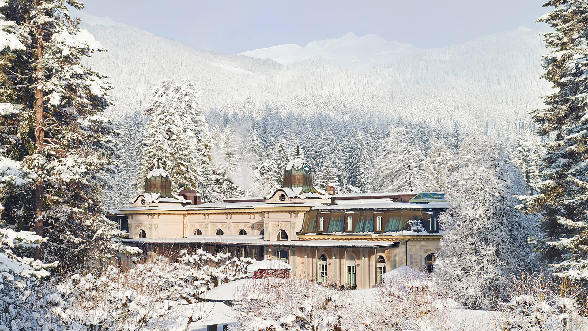 post card like beautiful winter scene of the Belle Epoque pavilion surrounded by snow covered trees and mountains, blue sky in the background