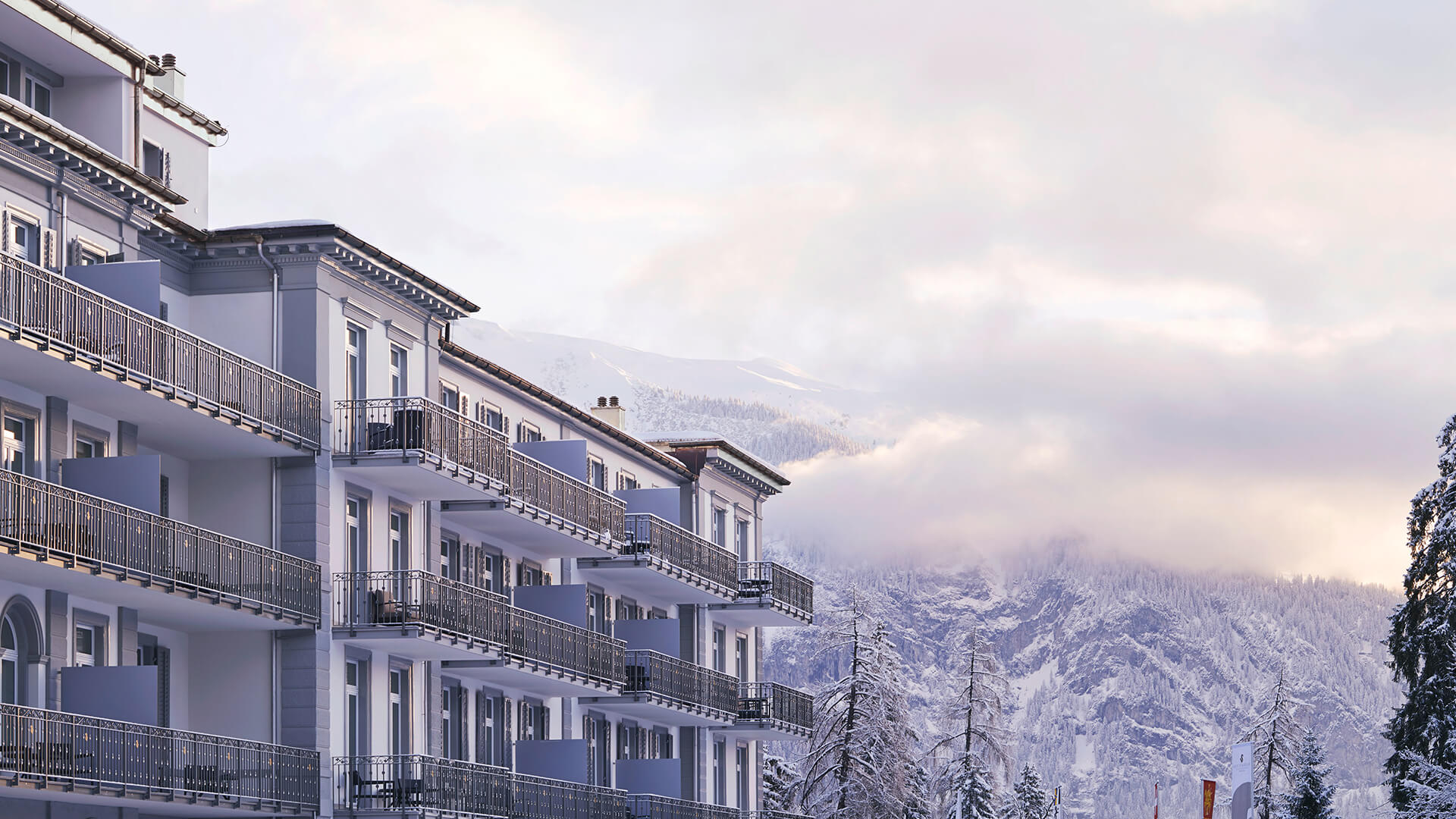 Grand hotel with partial cloud covered snowy mountains